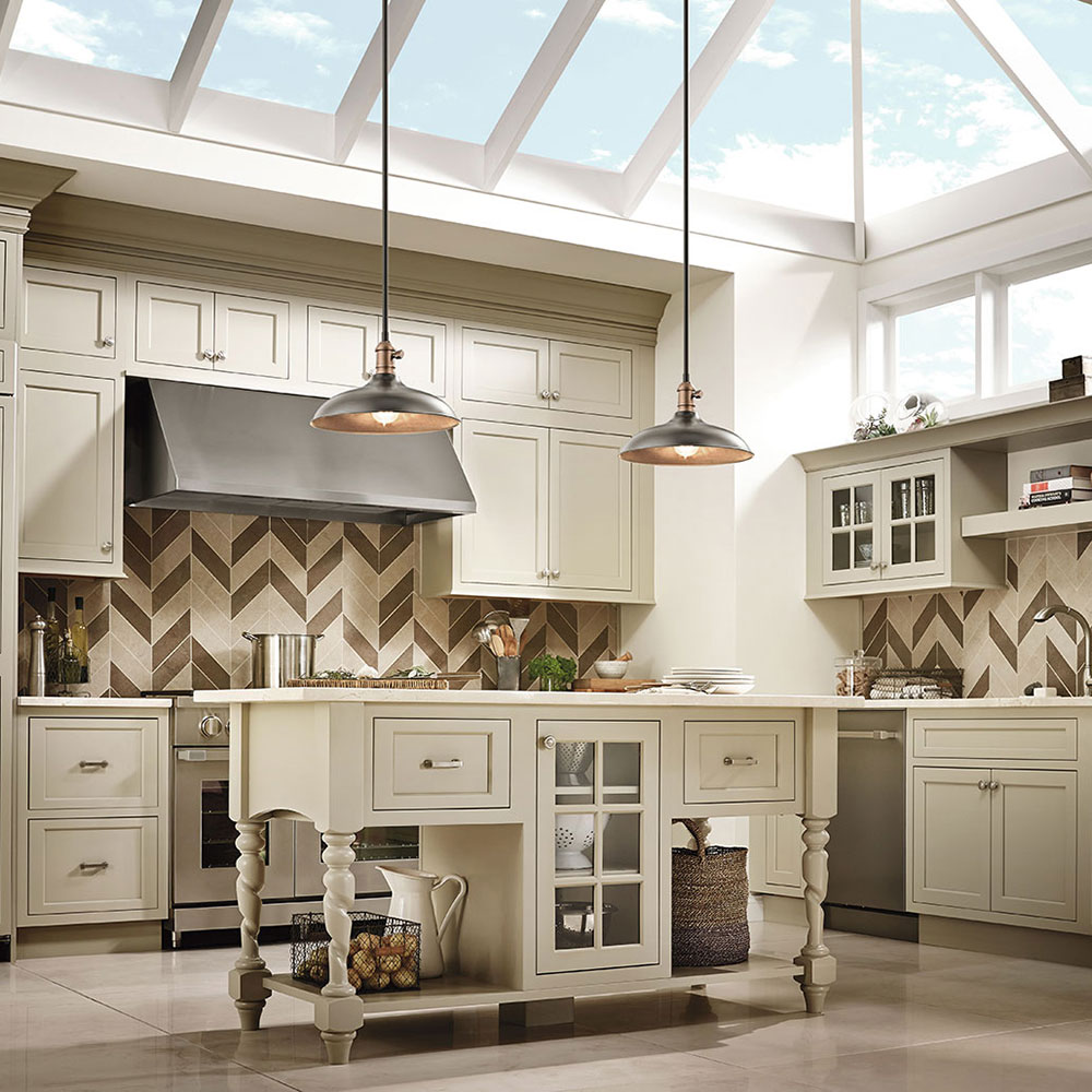 Kitchen with Traditional elements has rustic Kichler Natural Brass Pendants. The sky light adds so much light!