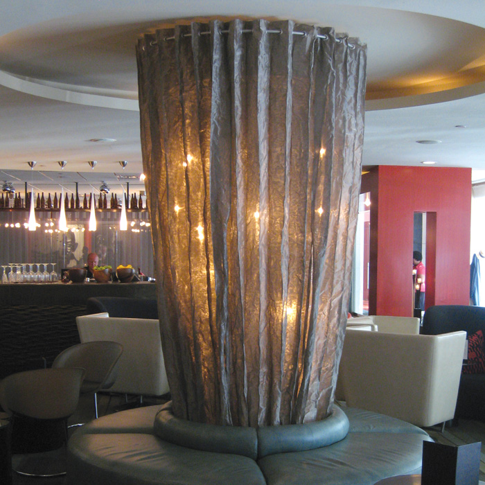 Fire Farm Diplomat 2059: This column curtain is a wonderful extrapolation of our signature metal mesh shade material into a one-of-a-kind sculptural lighting solution. The designer was faced with a very dominant structural column in the middle of the lobby of this well-known DC hotel near the Capitol building. After visiting our online gallery, they envisioned using our stainless steel mesh to wrap the column in a transparent curtain glowing with floating fireflies of light from within. The client was able to provide a remarkable photo-realistic rendering of the proposed construction in its environment.