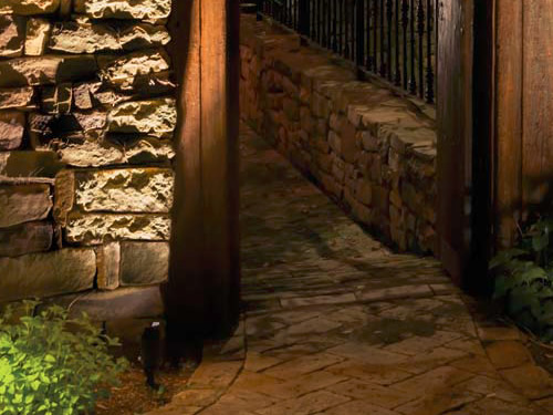 Landscape accent lights graze the stone wall. The shroud keeps any backwash from the light out of our eyes. - Landscape Lighting Beam Spread and Light Control: Light where you want it