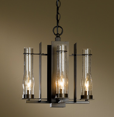 Hubbardton Forge New Town Wrought-Iron Chandelier hand-forged in Vermont, USA using the same techniques blacksmiths have used for centuries. The seeded glass hurricane shades are reminiscent of candle holders and oil lanterns before electricity.