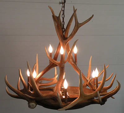This chandelier from the Peak Antler Company provides a beautiful amber glow through the mica tiers while retaining a rustic elegance feel of an antler chandelier. Medium and small elk antler circle the center with tall patina coated copper sleeves for the 9 candles. This chandelier is custom built by the artist in Colorado USA.