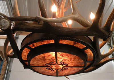 This chandelier provides a beautiful amber glow through the mica tiers while retaining a rustic elegance feel of an antler chandelier. Medium and small elk antler circle the center with tall patina coated copper sleeves for the 9 candles. This chandelier is custom built by the artist in Colorado USA.
