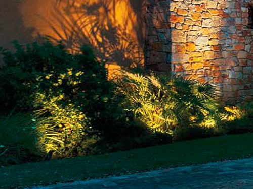 Kichler landscape lights remain invisible, just the landscaping is highlighted with the shadow of the plantings on the wall. - Landscape Lighting Beam Spread and Light Control: Light where you want it