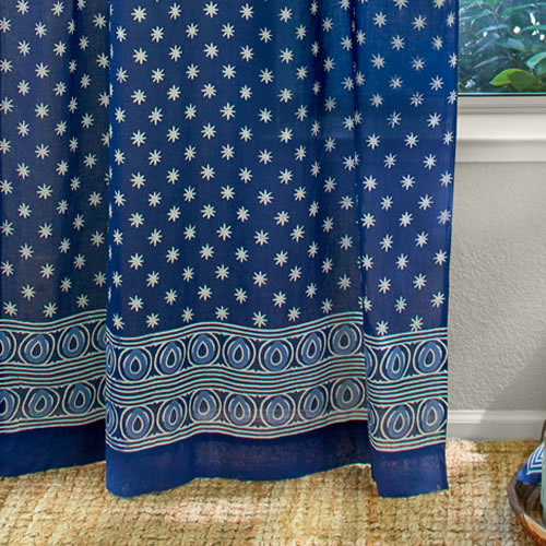 Saffron Marigold Starry Nights: A stunning batik print with a striking off-white star like patterning grounded in deep indigo blue.