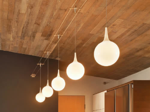 Tech Lighting Pele pendants suspended from Tech Lighting Kable run wall to wall below an exposed wood ceiling Lightweight pendants can be suspended from cable using the free-jack connector.
