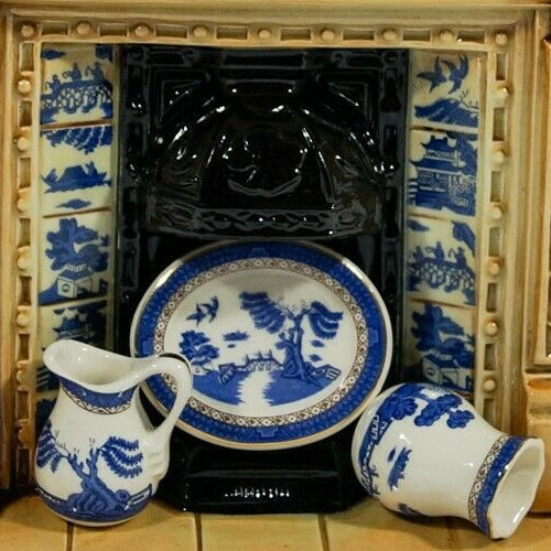 The hearth has Blue Willow Tiles and a plate, pitcher and vase with the Royal Doulton Old Willow Pattern