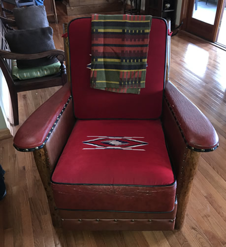 This looks like a Marc Taggart club chair with red wool Chimayo weavings on the cushions, leather and nail heads at the Auction Preview at Indian Cave Lodge