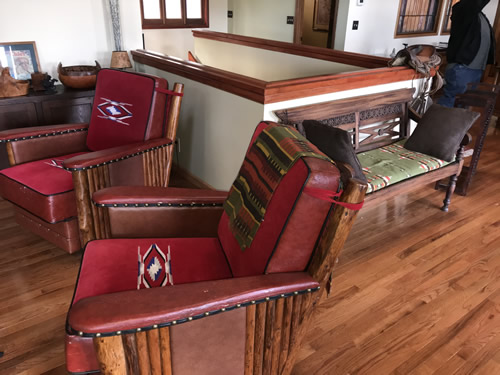 This looks like a Marc Taggart club chairs with red wool Chimayo weavings on the cushions, leather and nail heads at the Auction Preview at Indian Cave Lodge