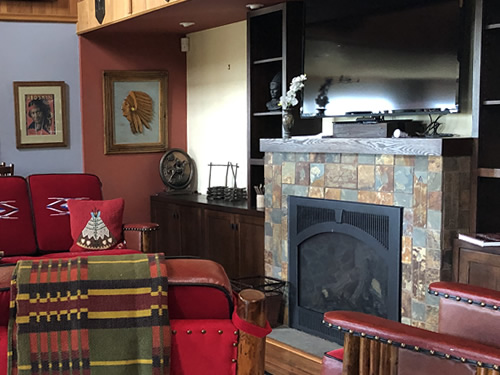 Fireplace, cowboy furniture and framed Indian pictures